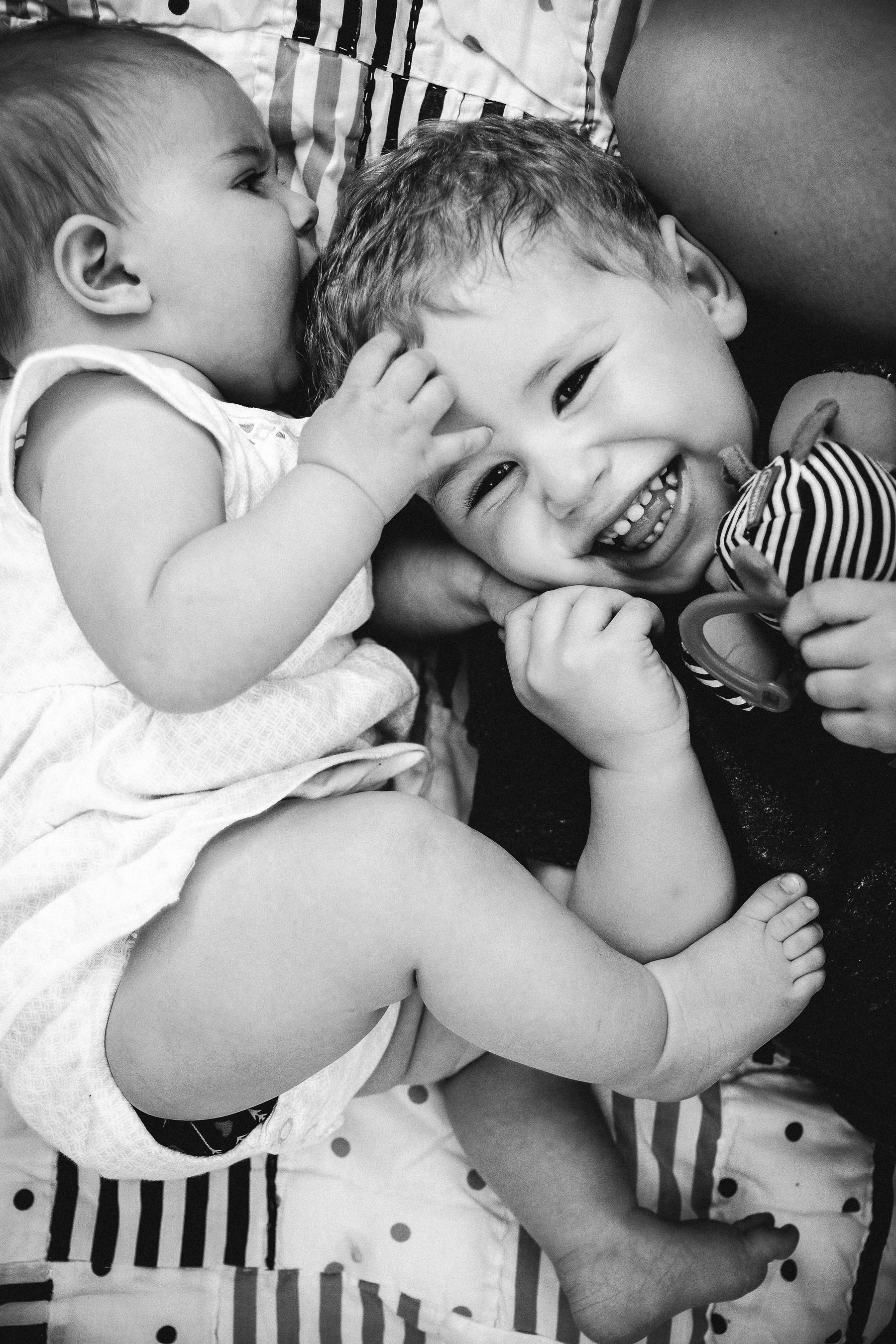 photo-d-un-bebe-couche-par-terre-qui-embrasse-son-frere-qui-rit-photographe-lifestyle-famille-et-nouveau-ne-a-montreal-marianne-charland-1.jpg