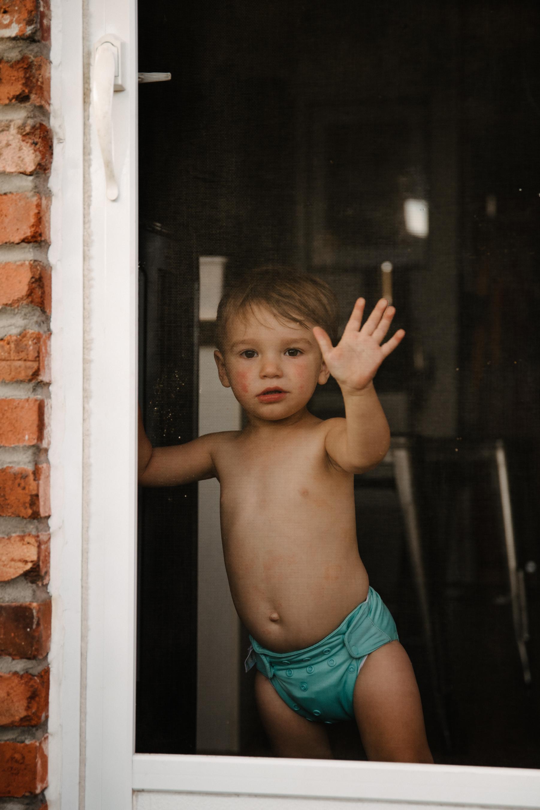 photo-d-un-enfant-en-couche-par-une-porte-moustiquaire-photographe-lifestyle-famille-et-nouveau-ne-a-montreal-marianne-charland-076.jpg