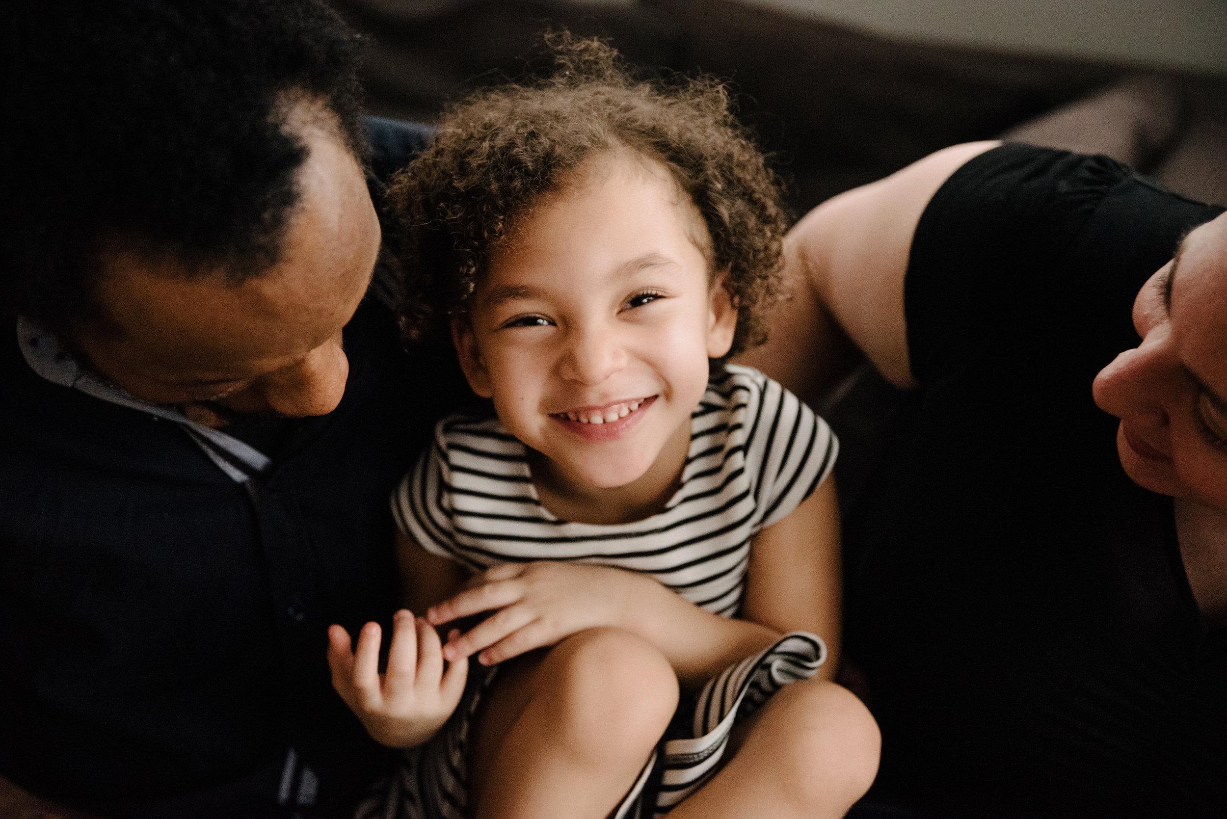 photo-d-une-fillette-au-sourire-rayonnant-blottie-contre-ses-parents-photographe-lifestyle-famille-et-nouveau-ne-a-montreal-marianne-charland-690.jpg