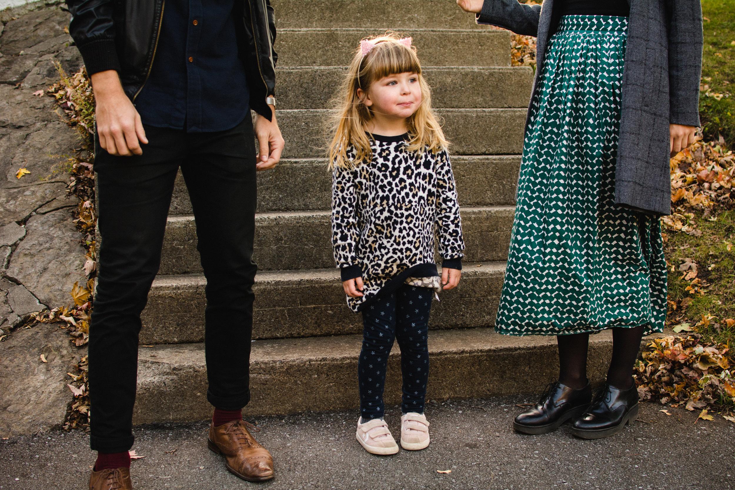 photo-d-une-fillette-espiegle-debout-entre-ses-parents-pere-photographe-lifestyle-famille-et-nouveau-ne-a-montreal-marianne-charland-024.jpg