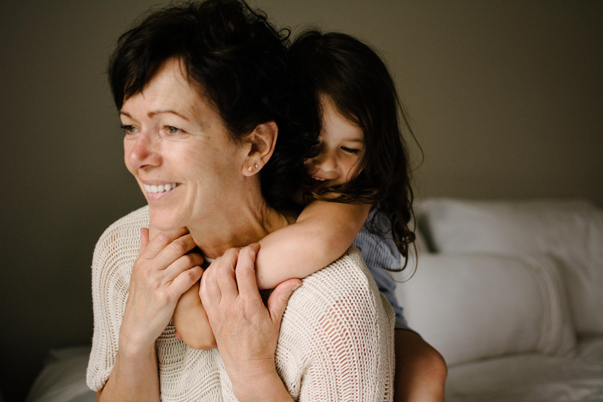 photo-d-une-petite-fille-accrochee-sur-le-dos-de-sa-grand-maman-qui-sourit-photographe-lifestyle-famille-et-nouveau-ne-a-montreal-marianne-charland-377.jpg
