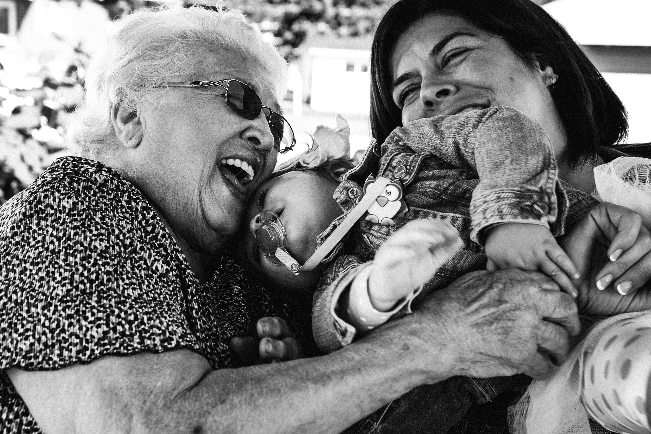 photo-noir-et-blanc-d-une-grand-maman-qui-rigole-avec-son-arriere-petite-fille-et-sa-mere-photographe-lifestyle-famille-et-nouveau-ne-a-montreal-marianne-charland-.jpg