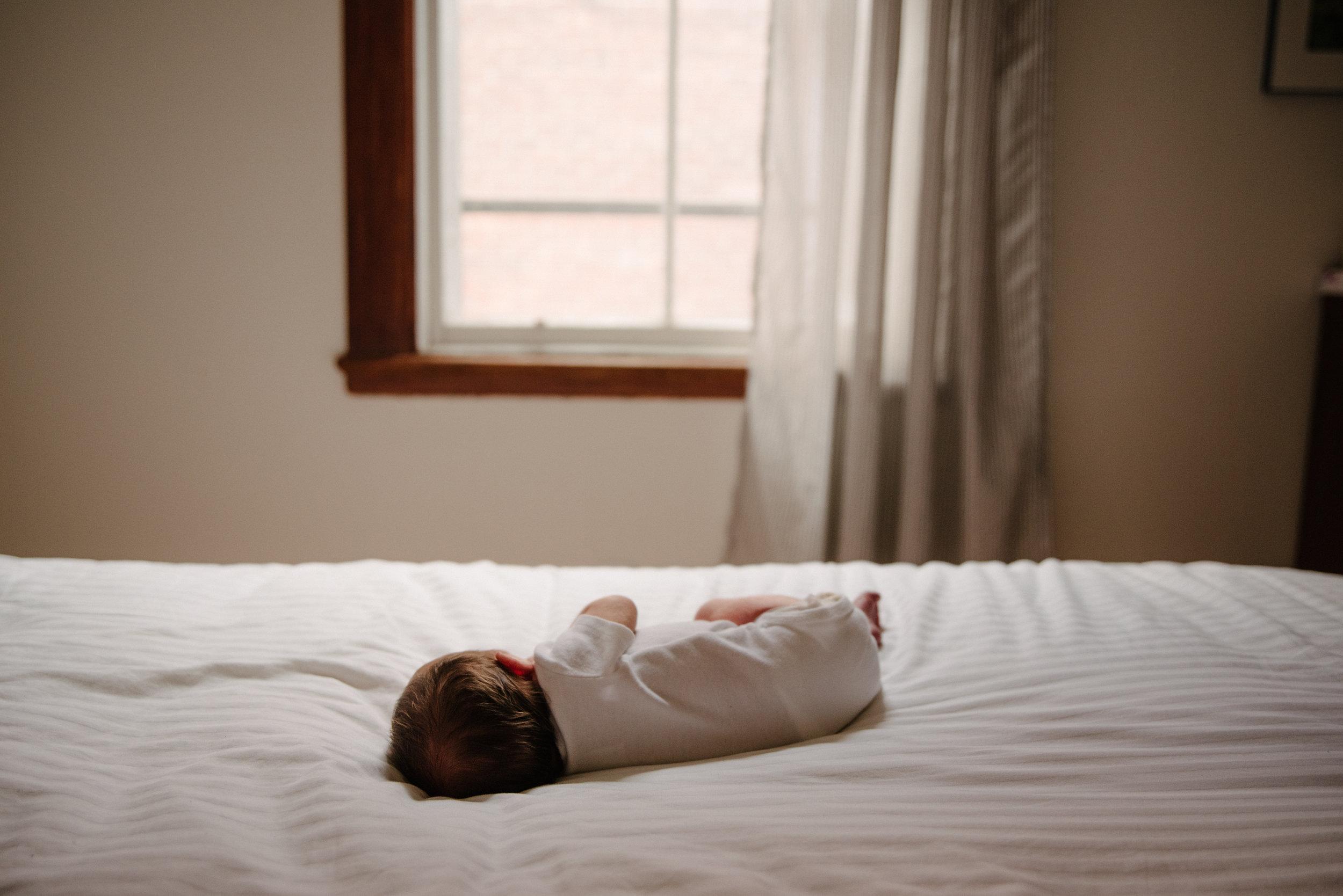 04-photo-lumineuse-d-un-bebe-etendu-sur-un-lit-devant-une-fenetre-photographe-lifestyle-famille-et-nouveau-ne-a-montreal-marianne-charland-590.jpg