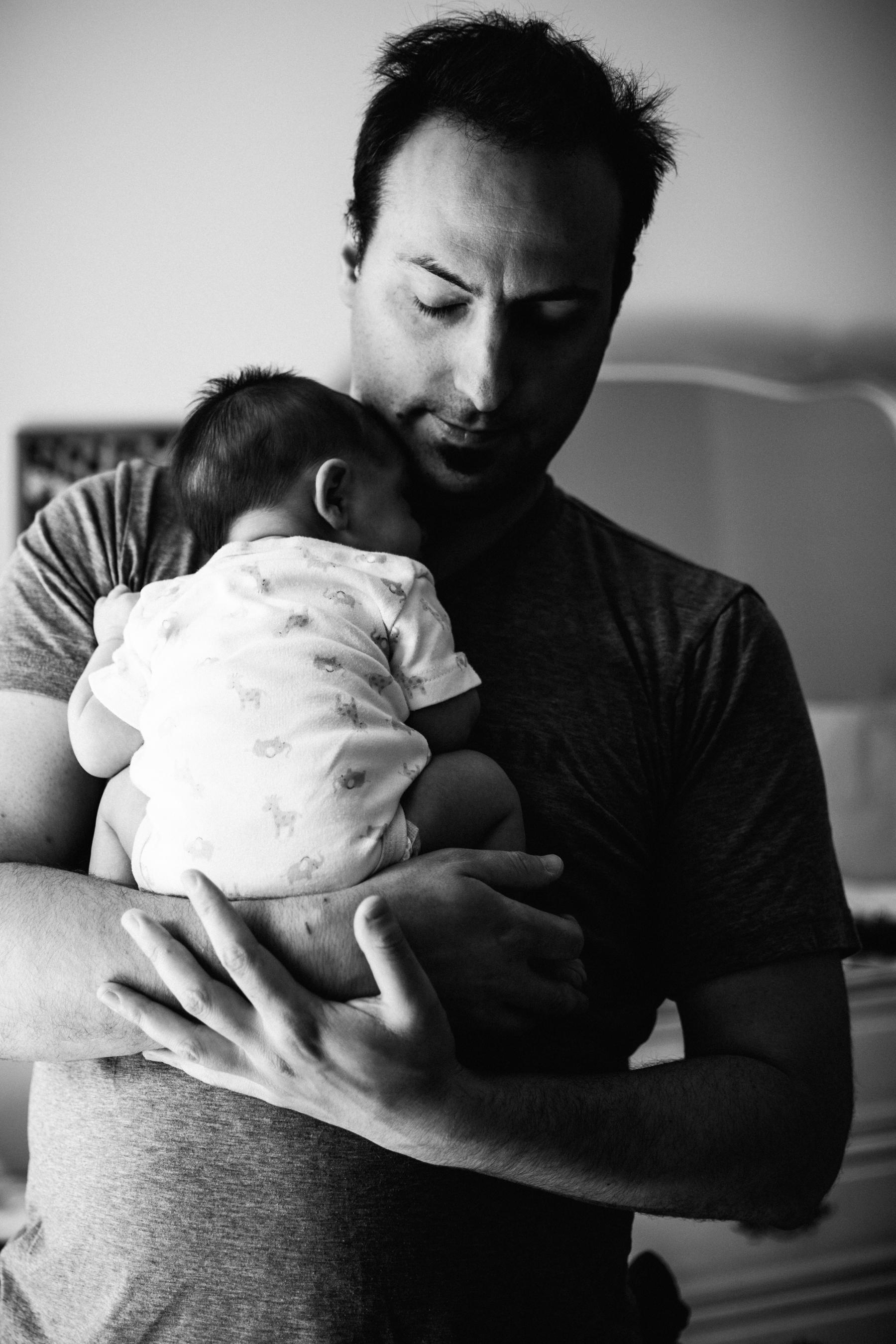 010-photo-noir-et-blanc-dun-papa-qui-tient-son-bebe-en-boule-contre-sa-poitrine-photographe-lifestyle-famille-et-nouveau-ne-a-montreal-marianne-charland-63.jpg