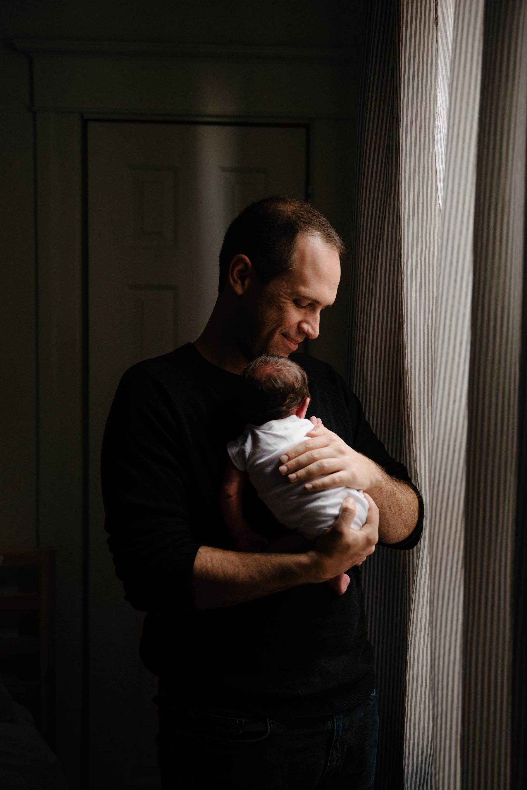 022-photo-d-un-nouveau-papa-fier-qui-tient-son-bebe-dans-ses-bras-photographe-lifestyle-famille-et-nouveau-ne-a-montreal-marianne-charland-388.jpg
