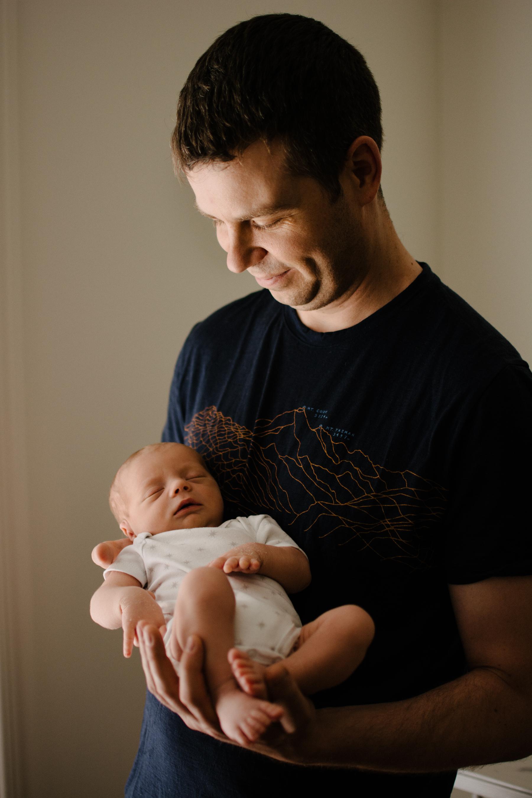 025-photo-d-un-papa-qui-tient-et-regarde-son-bebe-endormi-photographe-lifestyle-famille-et-nouveau-ne-a-montreal-marianne-charland-081.jpg