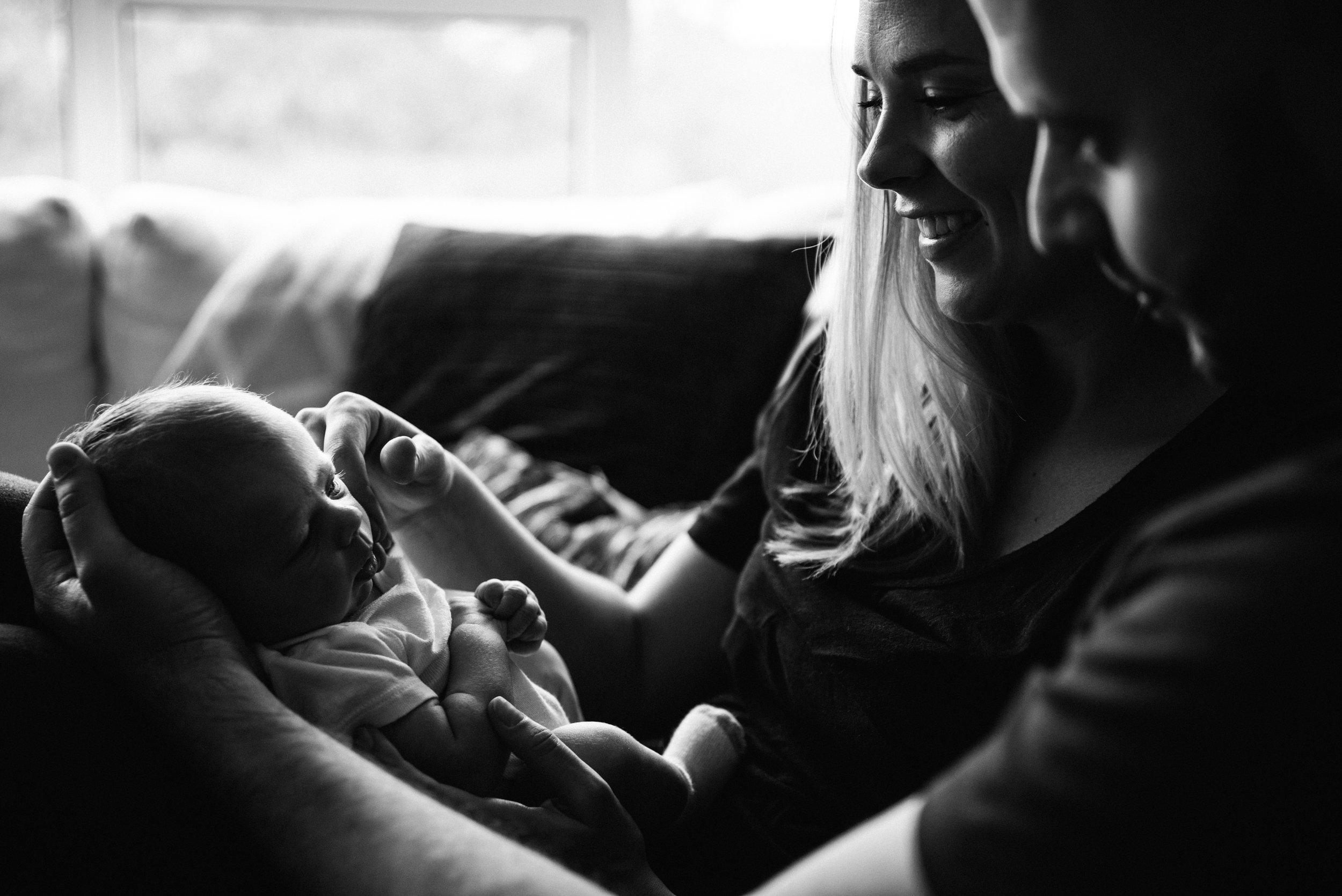 026-photo-noir-et-blanc-de-nouveaux-parents-qui-admirent-leur-bebe-assis-sur-leurs-genoux-photographe-lifestyle-famille-et-nouveau-ne-a-montreal-marianne-charland-088.jpg