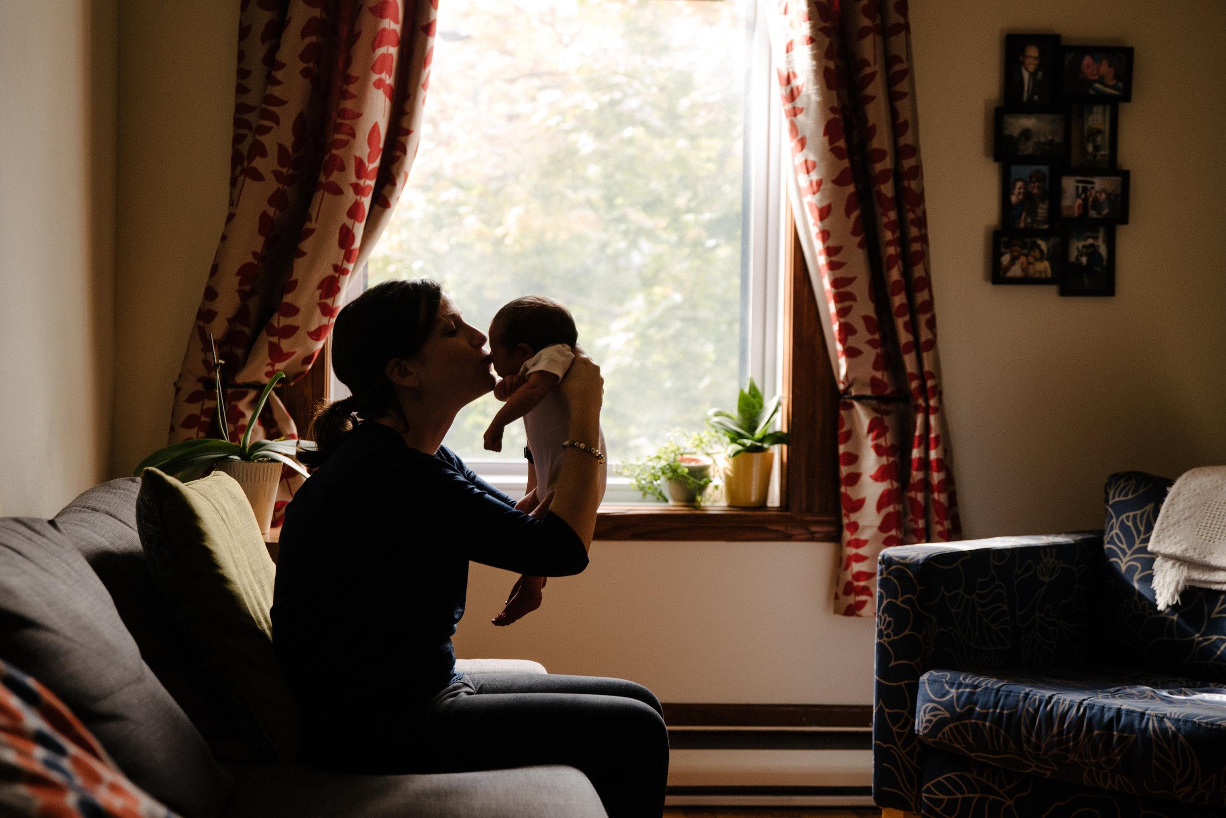 030-photo-d-une-maman-qui-souleve-et-embrasse-son-petit-bebe-sur-le-front-photographe-lifestyle-famille-et-nouveau-ne-a-montreal-marianne-charland-076.jpg