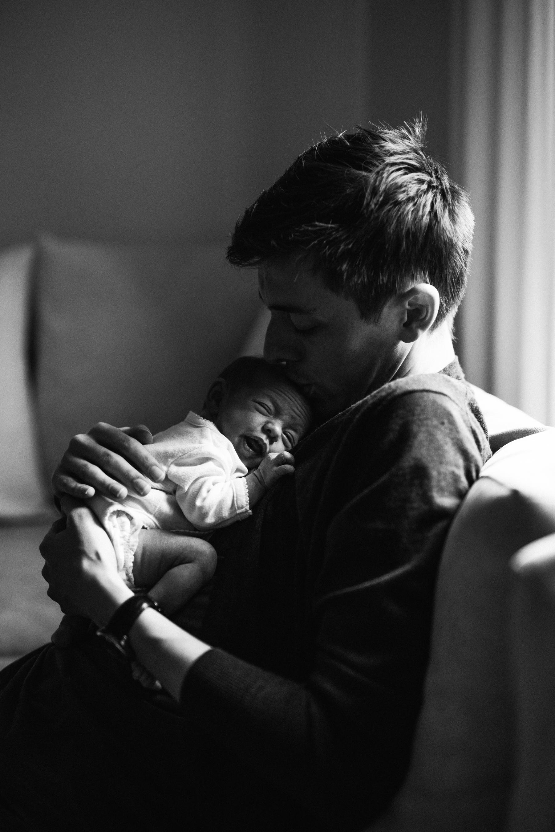 033-photo-noir-et-blanc-d-un-pere-qui-embrasse-son-bebe-qui-grimace-photographe-lifestyle-famille-et-nouveau-ne-a-montreal-marianne-charland-125.jpg