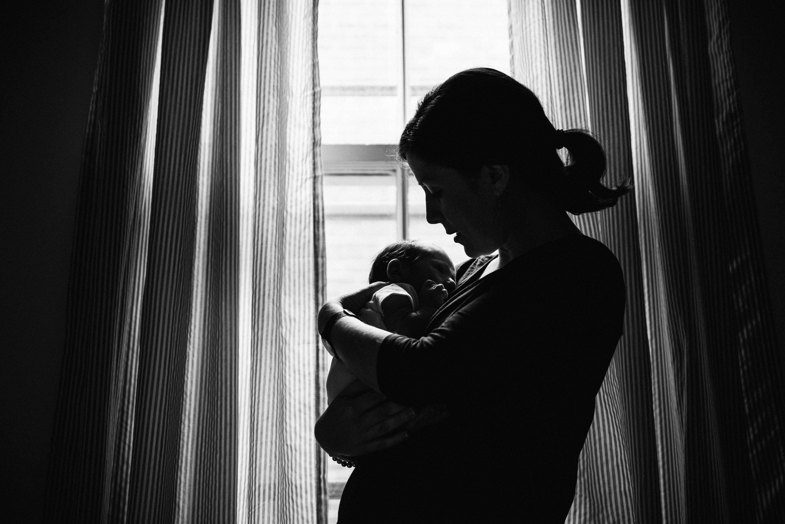 045-photo-noir-et-blanc-d-une-maman-qui-tient-tendrement-son-bebe-dans-ses-bras-devant-une-fenetrephotographe-lifestyle-famille-et-nouveau-ne-a-montreal-marianne-charland-424.jpg