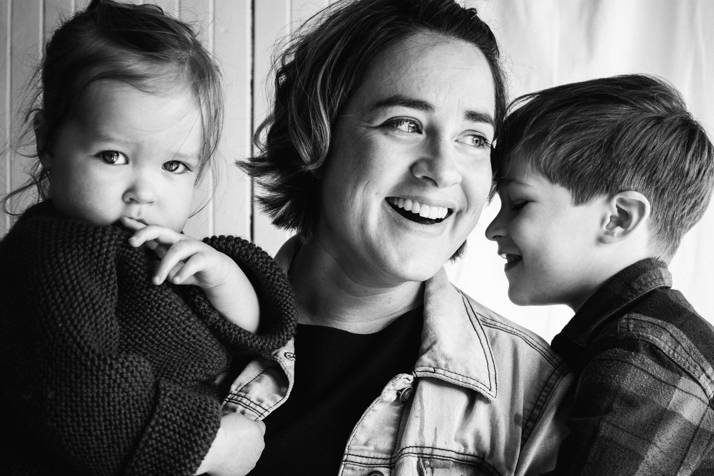 photo-noir-et-blanc-d-une-mere-souriante-avec-ses-deux-enfants-dans-les-bras-photographe-famille-a-montreal-cadeau-fete-des-meres-14.jpg