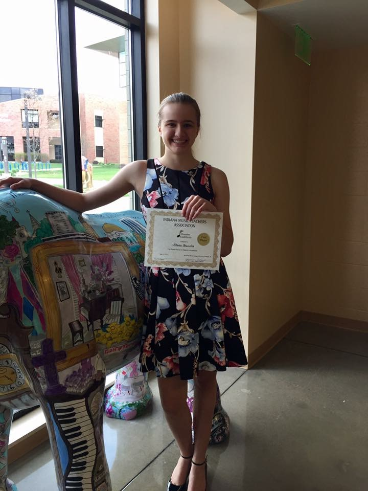 Olivia Bressler, one of Alicia's first students, holding up her award