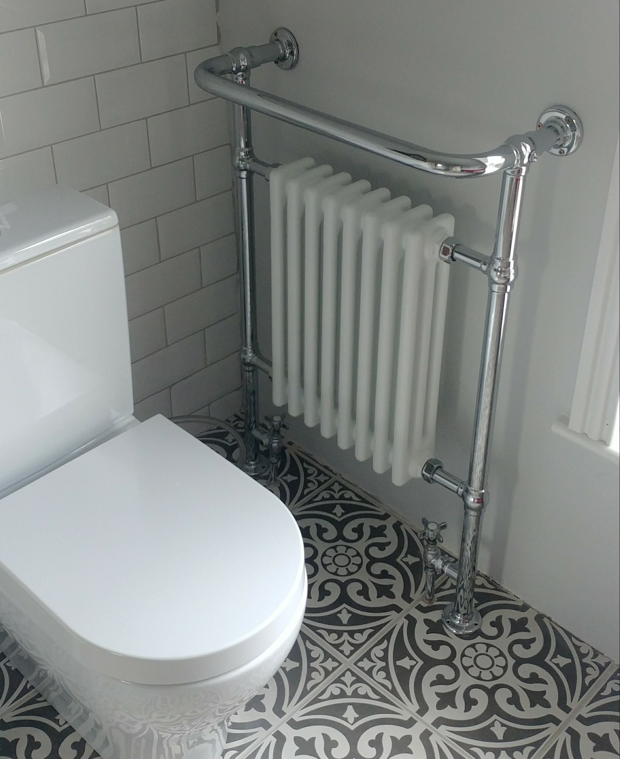I love the juxtaposition of the modern lines of the WC with the classic curves of the radiator.