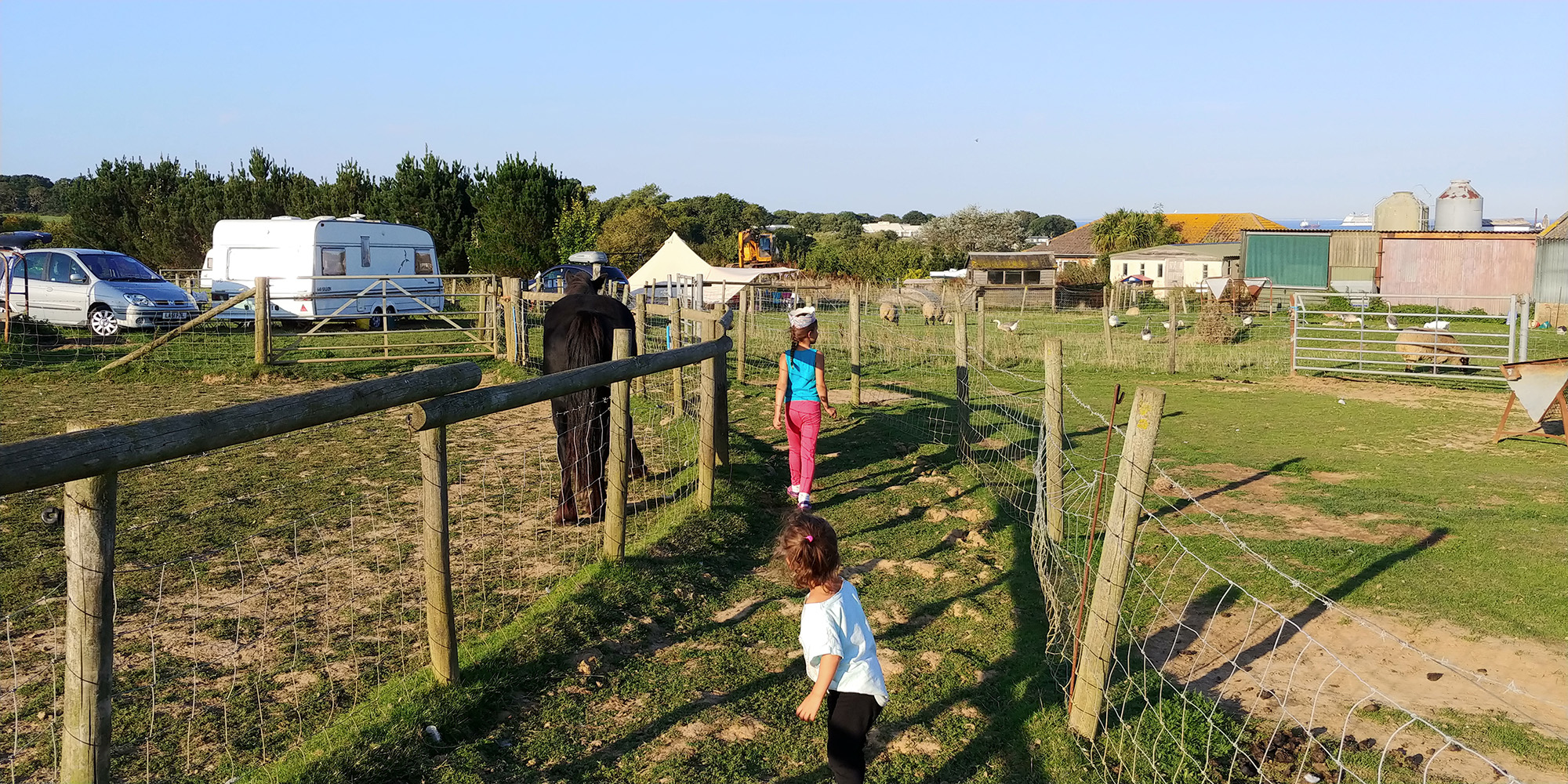 Our biggest and smallest girl exploring the paths around the farm. You can see the point of our tent in the background.