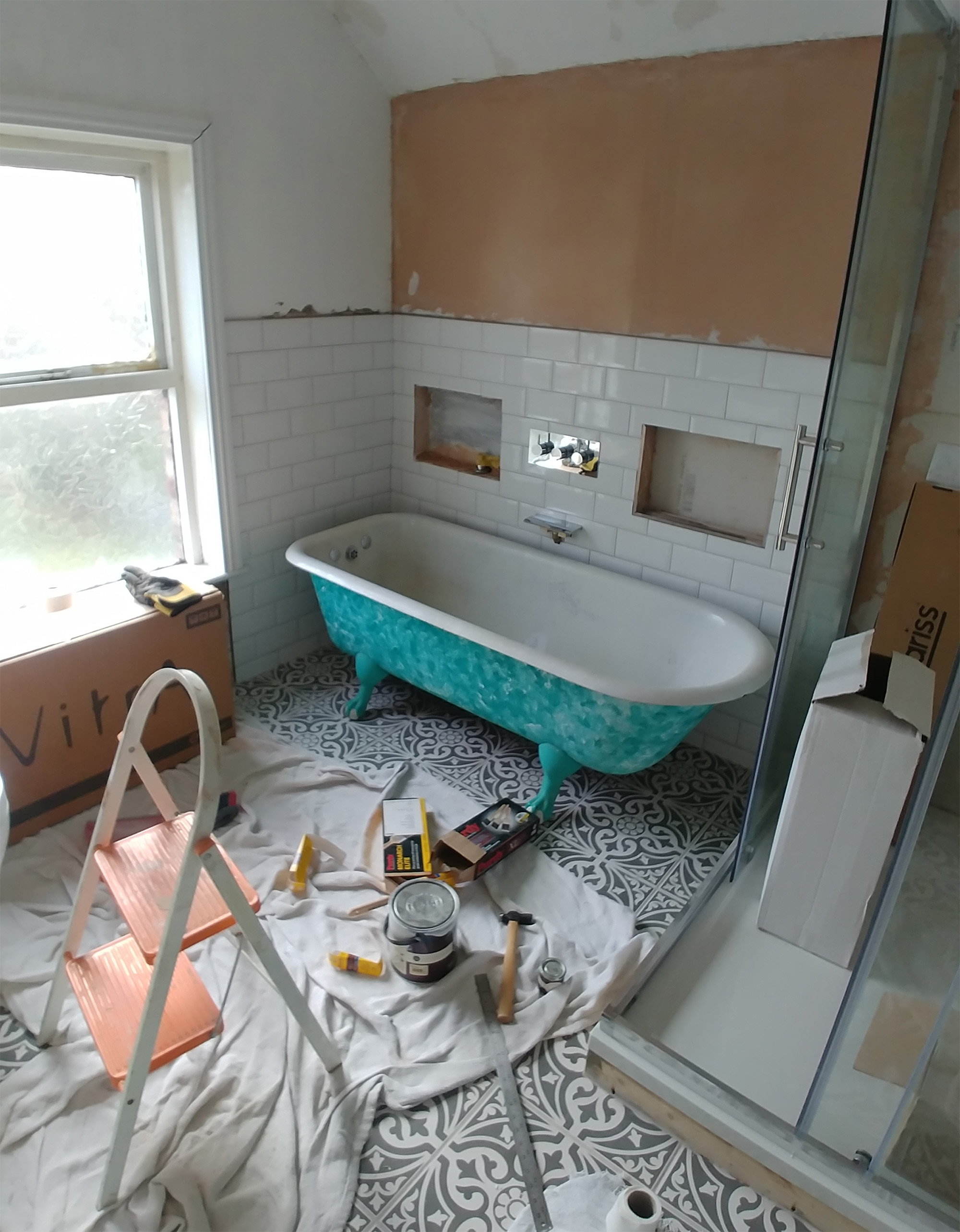 Floor, wall tiles and shower surround done. Shower tiles, sink, bath and decorating yet to do.