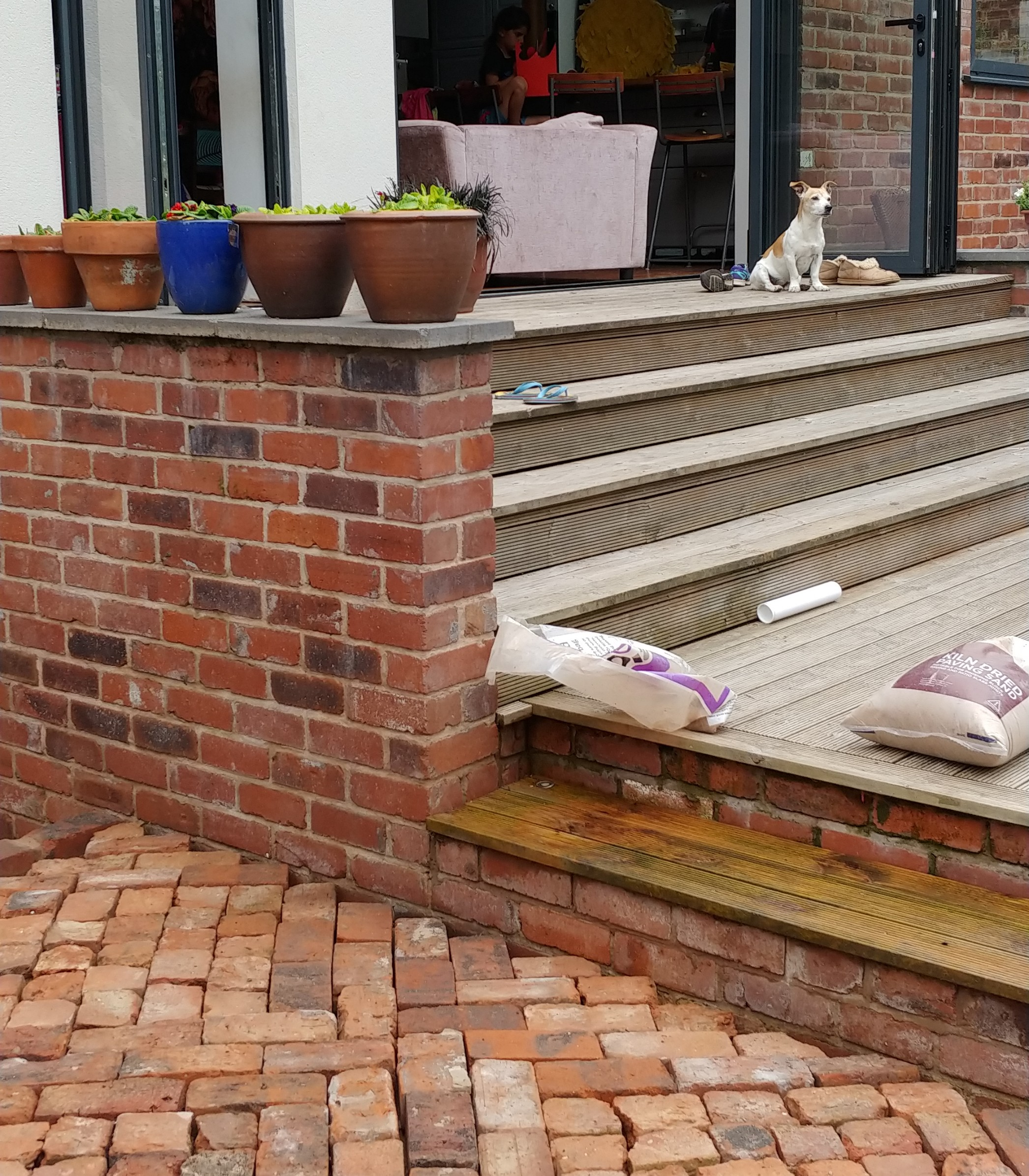 Our brick patio against our reclaimed brick wall (built by the builders) leading up to our main deck and bifolds.