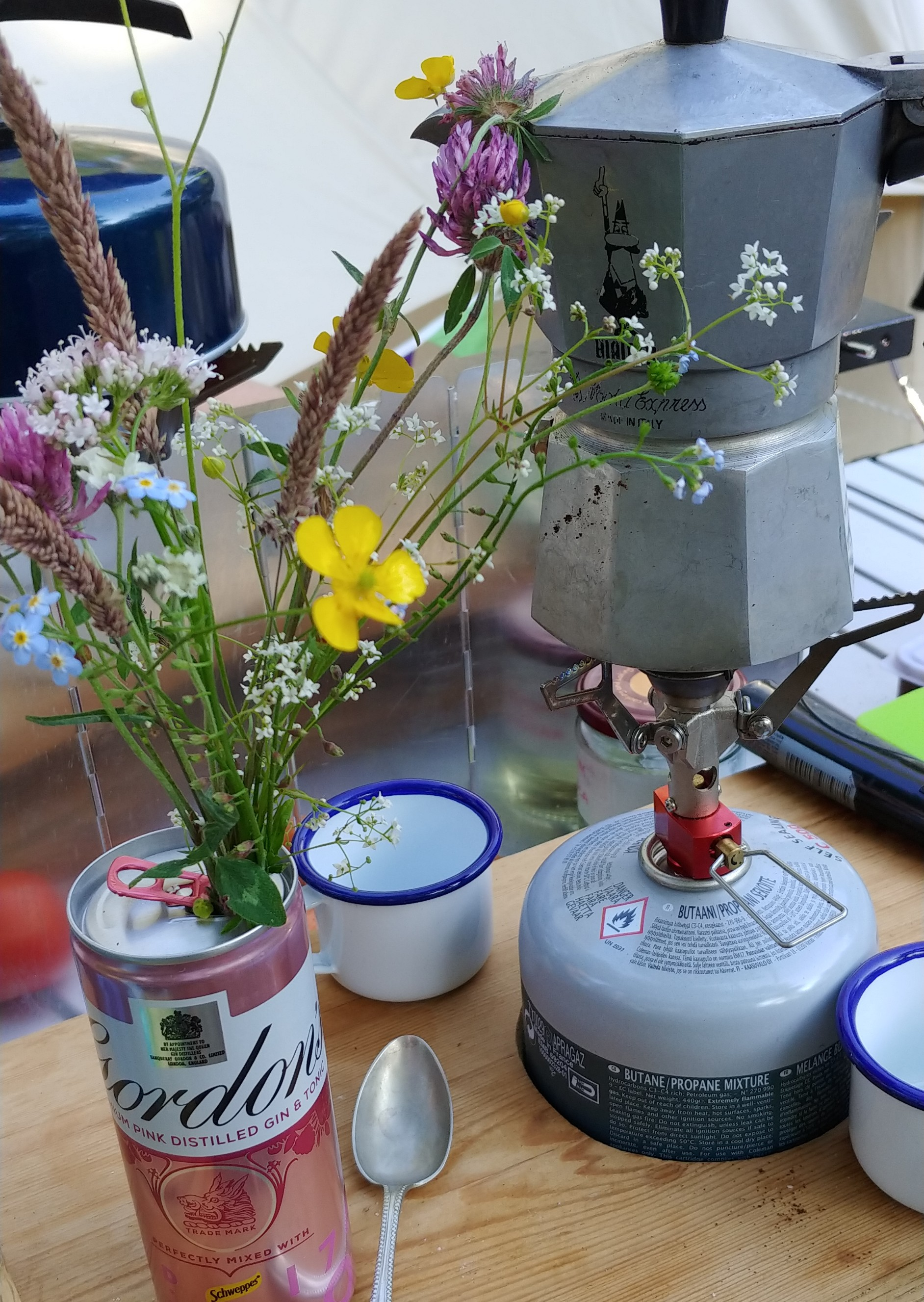 Camping kitchen style - wildflowers in a gin tin, antique tea spoons, our little pocket rocket, a Moka pot, and enamel espresso cups.