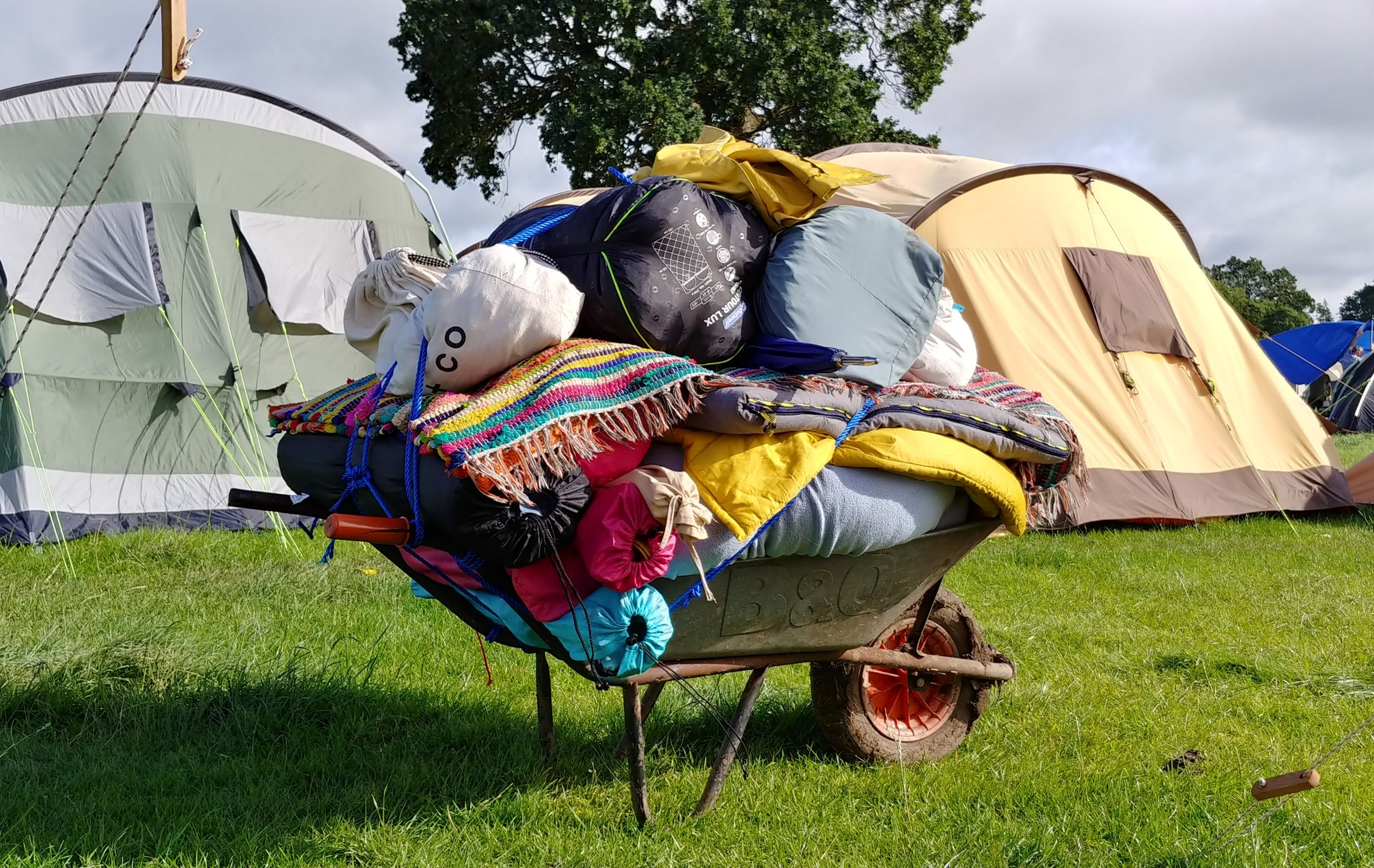 Rug, pillows, sleeping mats, chairs, sleeping bags, sacks of clothes and blankets.