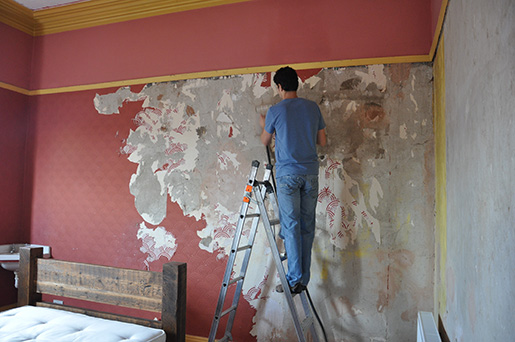 Taking the wallpaper off, along with most of the plaster underneath.