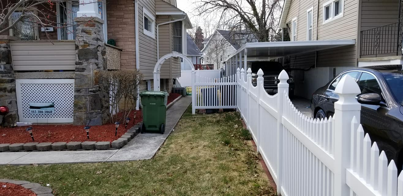 A white PVC fence with vertical slots