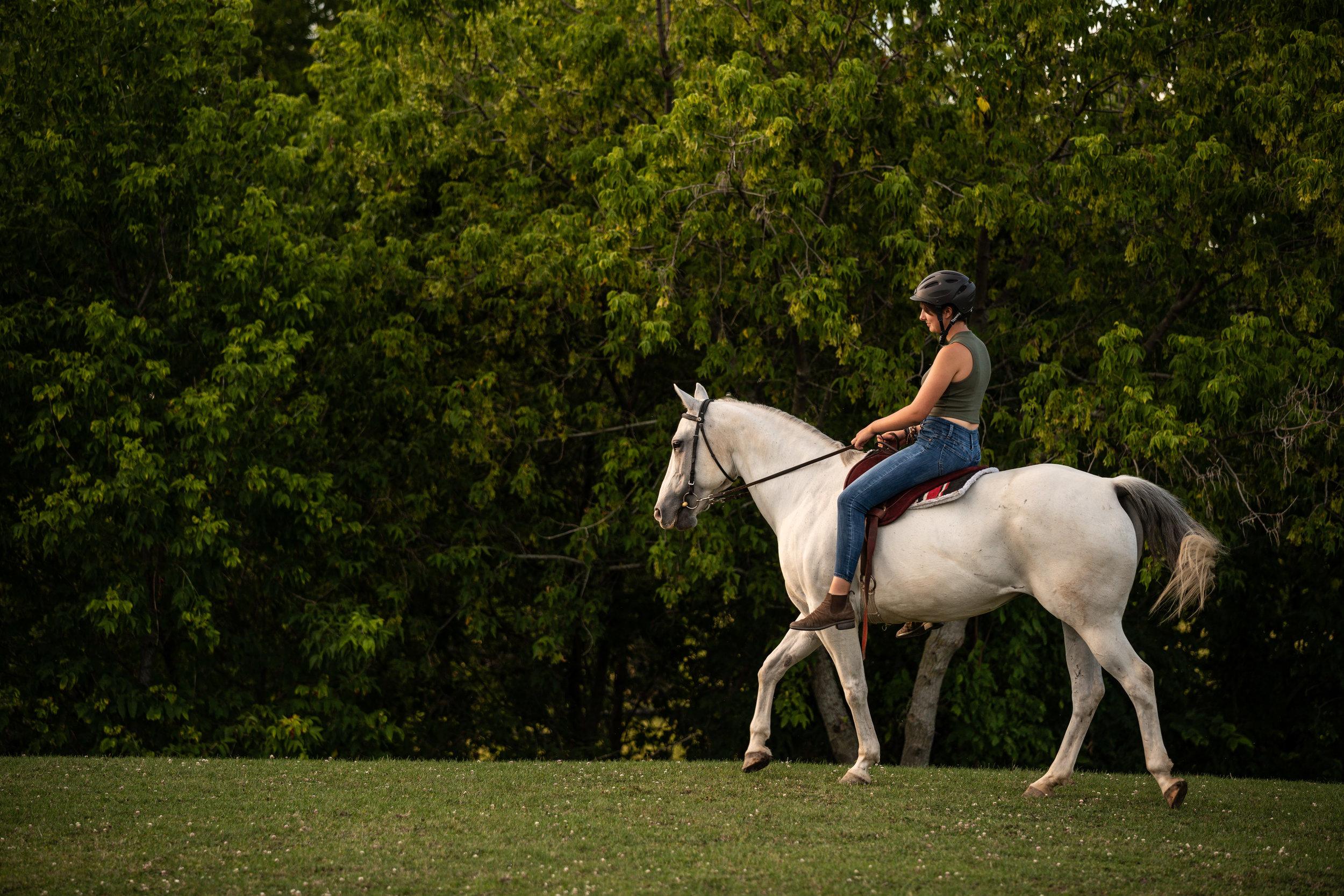 A girl riding a grey quarter horse