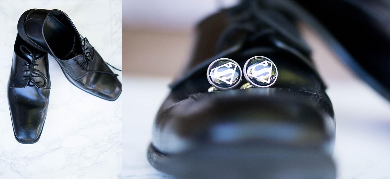 Grooms slick black shoes with super hero cufflinks.