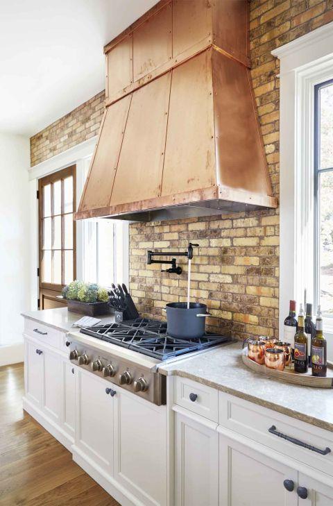 Rustic copper hood over a 6-burner range