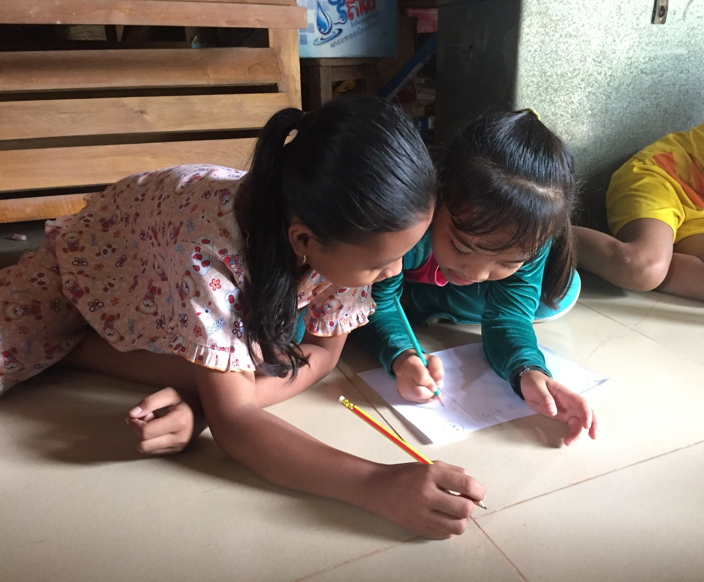 Two children complete the H-Method Worksheet during a Focus Group Discussion in Cambodia.