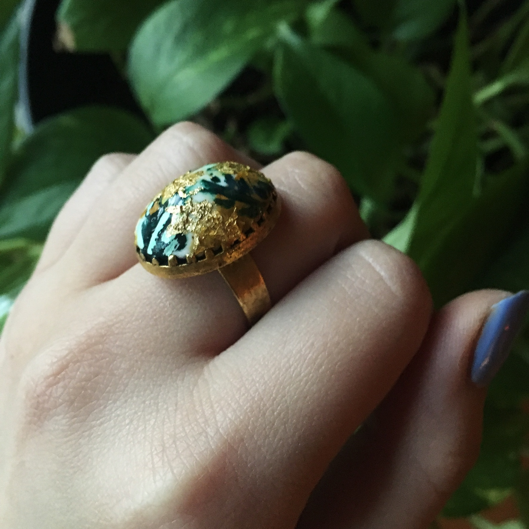 A brass and polymer clay oval ring in a decorative setting with gouache and gold leaf detailing.