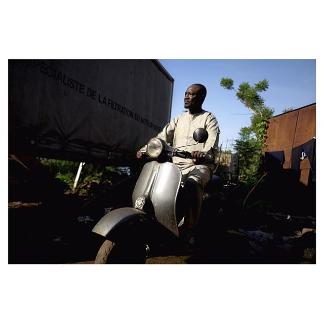 """""""Passion Vespa à Bamako""""  Seydou Seck poses on his Vespa 150 sprint produced in 1969.  In Bambara, the most widely spoken language in Mali, Vespa is nicknamed: """"Boo bara ba""""  that literally means """"Fat ass"""", because of its large rear shapes.  Text by @amauryha video by @srieussec  #vespa #bamako #mali #westafrica #piaggio #onassignment #reportage #reportagespotlight #photodocumentary #photojournalism #afp #afpphoto"""