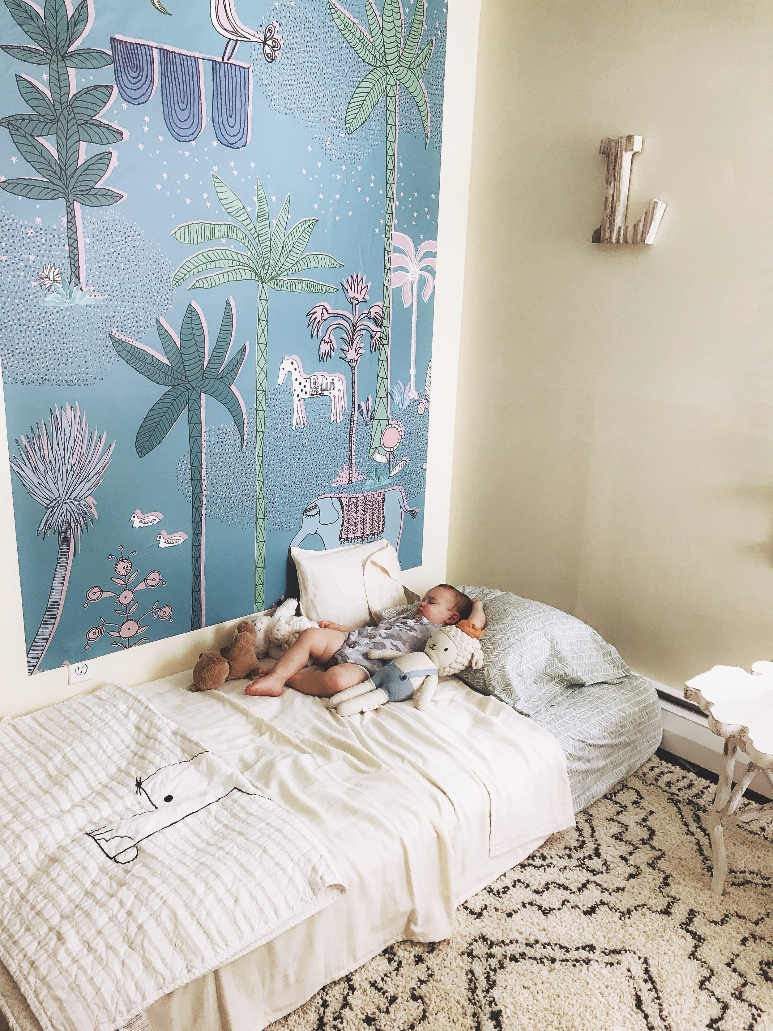 Wall decal is  Pottery Barn Kids , Gauze blanket is  Willaby , Sebastian the Lamb is  Cuddle & Kind  and his romper is  Childhoodsclothing