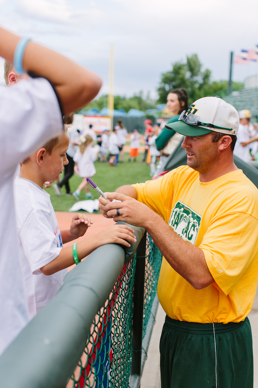 San Jacinto assistant coach Eric Weaver signs balls for young fans.