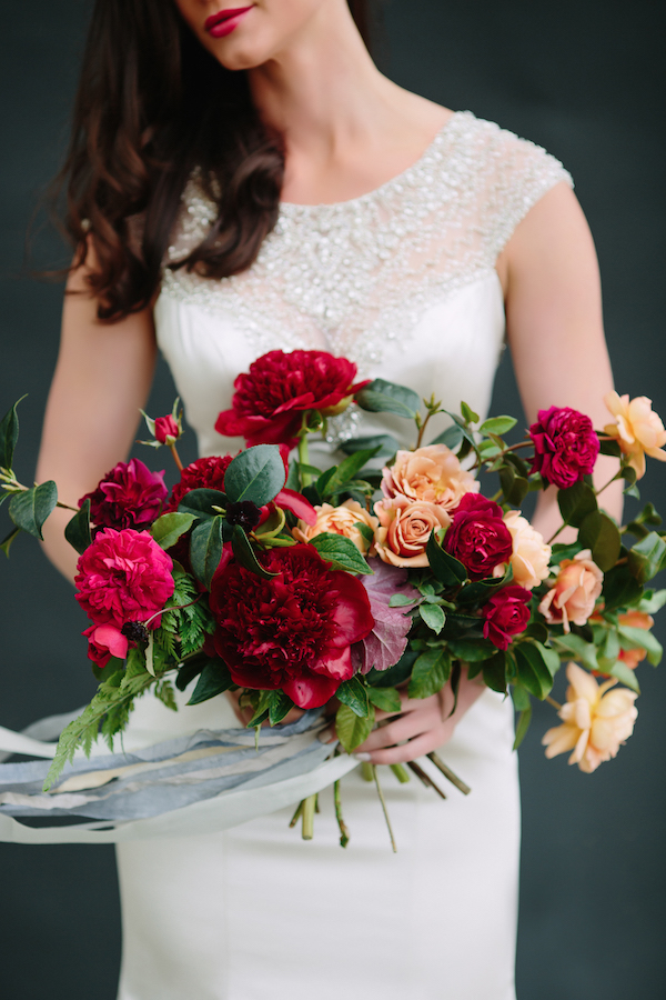 A dramatic summer wedding bouquet of garden roses, camellia, peony, and fern   Photo by  Cat Mayer