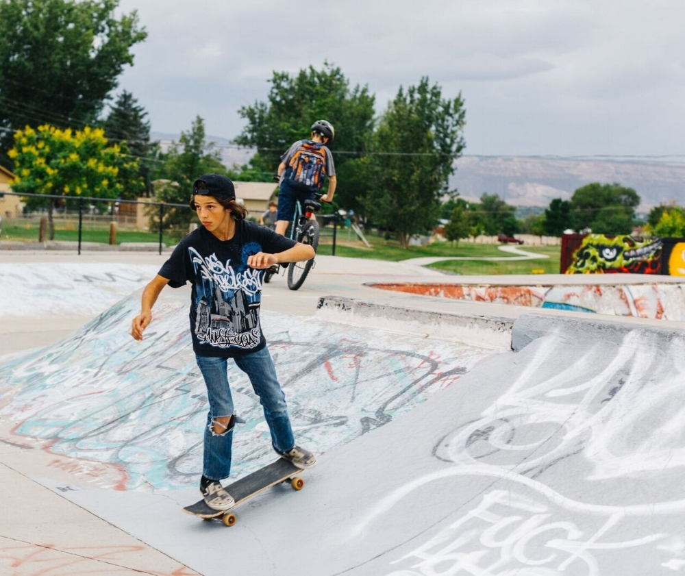 Teens skateboard, jump scooters, and ride bikes after school at Westlake Park Skatepark in Grand Junction. / Photo by Cat Mayer