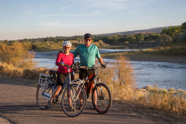 """""""Our e-bikes get us excited about going for long rides and bicycling up hills. It's great exercise. We have biked up to Maroon Bells, on many Grand Junction trails, and to and from church. The possibilities are endless! Many of our friends are graduating to e-bikes.""""    — David Mayer and Lynette Richardson biking along the Riverfront Trail in Grand Junction"""