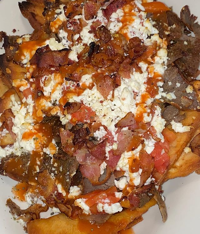 GREEK NACHOS... pita chips loaded with crispy gyro and bacon and covered in melted feta, topped with diced tomatoes, scallions, tzatziki and hot sauce