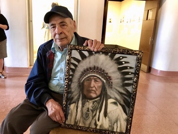 Artist Bill Gilham showing one of his portrait paintings.