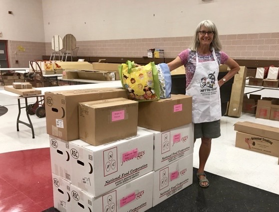 Sue Fletcher standing in KW Bergan School with school supply donations.