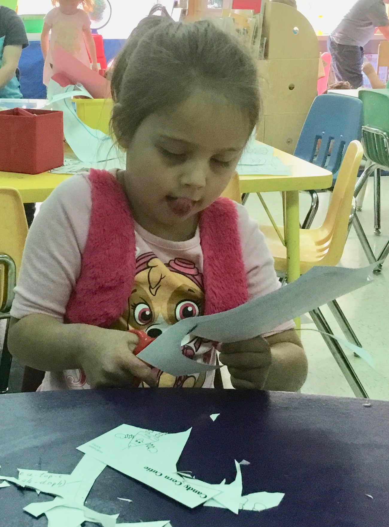 A Pre-K student concentrating really hard on using her donated scissors.