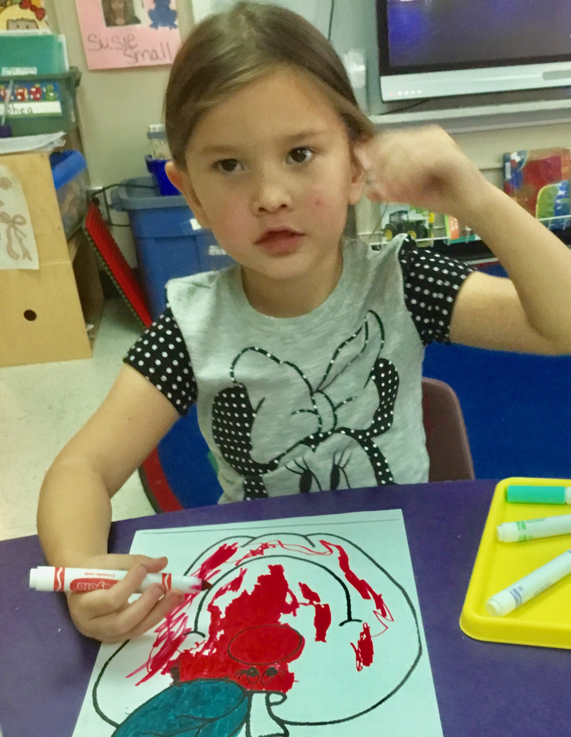 A Pre-K student colors with donated supplies.