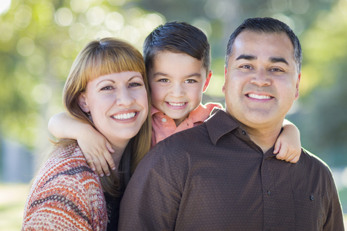 smiling couple with young son in the middle