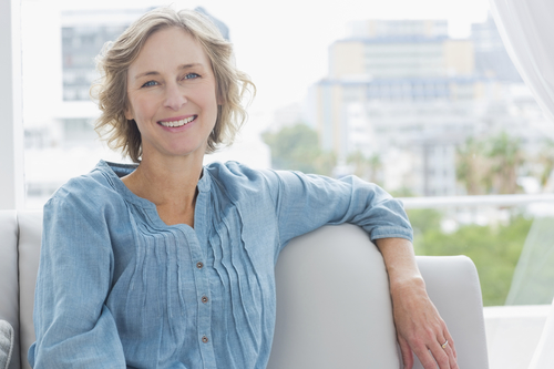 elderly woman sitting on couch in front of window smiling at camera