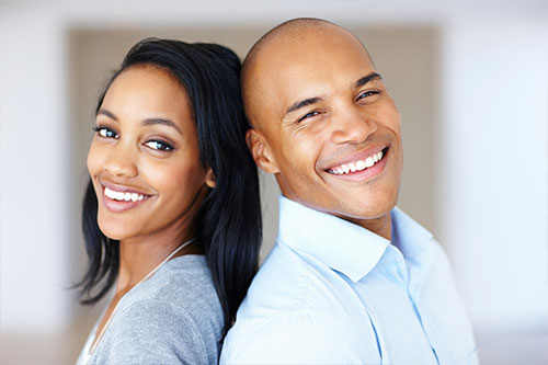 smiling young couple standing back to back looking at camera