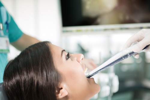 woman looking up at screen while doctor shows her teeth with camera