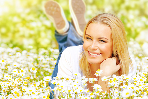 Pretty young woman lying down smiling in a dreamy field of flowers