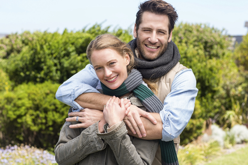 Young couple smiling at camera with man hugging woman from behind