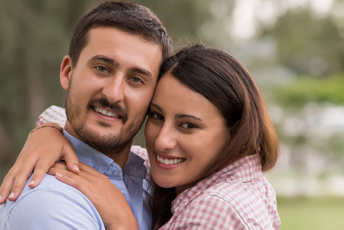 smiling couple forehead to forehead looking towards camera