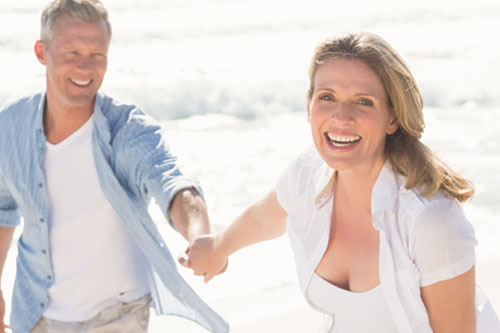 smiling middle aged couple laughing and running