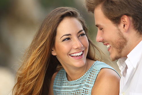 attractive young woman looking up smiling at young man