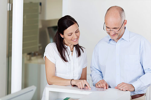 patient completing paperless forms at front desk with staff member